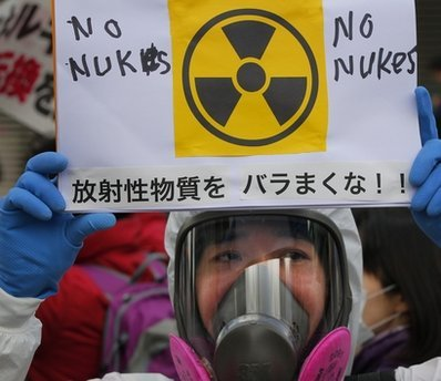 A protester in protective mask holds a placard during an anti nuclear rally in Tokyo, Sunday. (AP-Yonhap news)