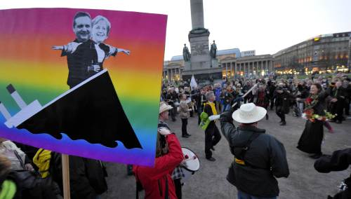 Green Party supporters dance in Castle Square in downtown Stuttgart, southern Germany on Sunday next to a poster showing German Chancellor Angela Merkel and the State Premier Stefan Mappus after the state elections in Baden-Wuerttemberg. (AFP-Yonhap News)