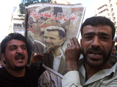 Syrians shout slogans for Assad, waving the president's image in Beirut on Sunday. (Xinhua-Yonhap News)