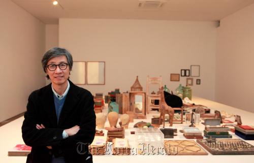 Koo Bohnchang in front of a table full of his private collection. (Kukje Gallery)