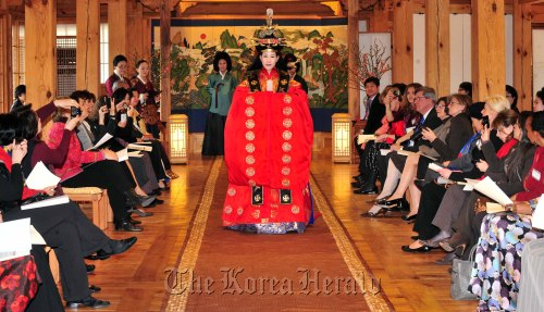 Spouses of foreign ambassadors and other participants watch a fashion show featuring Korean traditional wedding dresses at the Korea Furniture Museum in Seoul on Tuesday. (Kim Myung-sub/The Korea Herald)