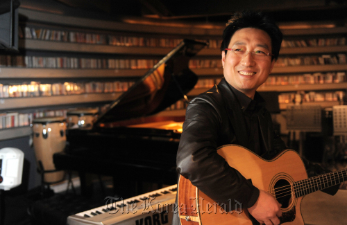 Leader of '80s band Five Fingers Lee Doo-heon talks about his blend of music and company structure while playing guitar at his jazz bar in Seorae village, Seoul. (Ahn Hoon/The Korea Herald)