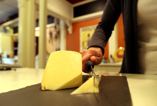 Erika Aylward, co-owner of Boulevard Market, cuts a piece of raw milk gouda cheese at her store in Tecumseh, Michigan, March 17. (Detroit Free Press/MCT)