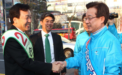 Sohn Hak-kyu (left), chairman of the main opposition Democratic Party, shakes hands with Kang Jae-sup, former leader of the ruling Grand National Party, as they met Friday while campaigning for the parliamentary by-election in Bundang, Gyeonggi Province. (Yonhap News)