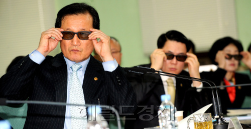 Finance Minister Yoon Jeung-hyun (left) takes a look at smart TV content with government officials at an economic policy meeting at the Gwacheon government complex on Wednesday. (Park Hyun-koo/The Korea Herald)