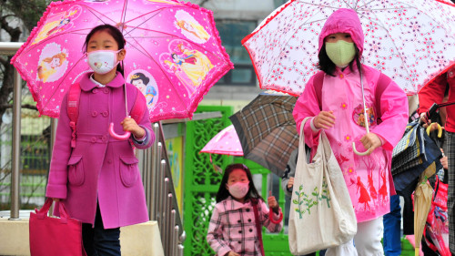 Children wearing masks and holding umbrellas go to school on Thursday amid fears that the rain may contain radioactive materials from the crippled nuclear reactors in Japan. (The Korea Herald)