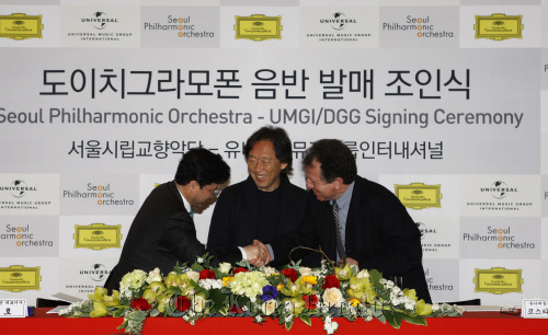 Seoul Philharmonic Orchestra music director Chung Myung-whun looks on as Universal Music Group International senior vice president Costa Pilavachi (right) and SPO CEO Kim Joo-ho shake hands after signing a long-term license agreement between the orchestra and UMGI's Deutsche Grammophon in Seoul on Thursday. (SPO)