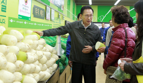 President Lee Myung-bak talks to a shopper about rising prices of farm and fishery products at the Hanaro Club in Seoul on Thursday. (Yonhap News)