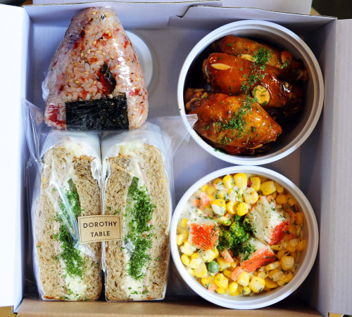 A mix-and-match packed meal from Dorothy Table featuring corn and crab salad, potato ham sandwich, chili buffalo wings and a pickled vegetable onigiri.