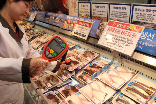 An inspector checks radiation levels of fish sold at a Lotte Mart branch in central Seoul, Sunday. (Yonhap News)