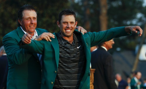 Phil Mickelson (left) helps Charl Schwartzel put on his green jacket after winning the Masters tournament. 9AP-Yonhap News)
