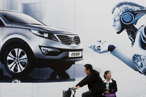 A couple cycles past a billboard outside the venue of the Auto Shanghai show in Shanghai on Thursday. (AFP-Yonhap News)