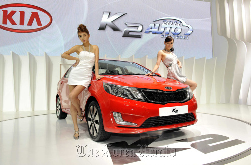 Models pose with Kia Motors Corp.'s K2 subcompact designed for the Chinese market at the Auto Shanghai 2011 in Shanghai on Tuesday. (Kia Motors Corp.)