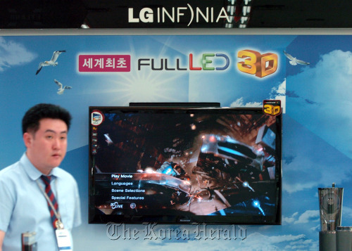 A salesclerk walks near a LG Electronics Inc. 3-D television at an electronics shopping mall in Seoul. (Bloomberg)