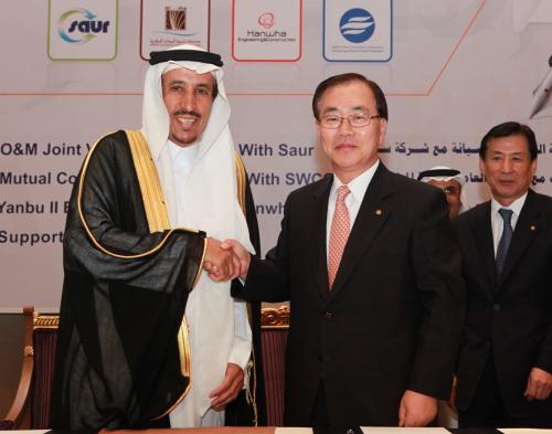 Hanwha Engineering & Construction CEO Kim Hyun-chung (right) and Saudi Arabia's prince Saud bin Abdullah shake hands after signing a contract in Jubail, Saudi Arabia, Tuesday. (Hanwha E&C)