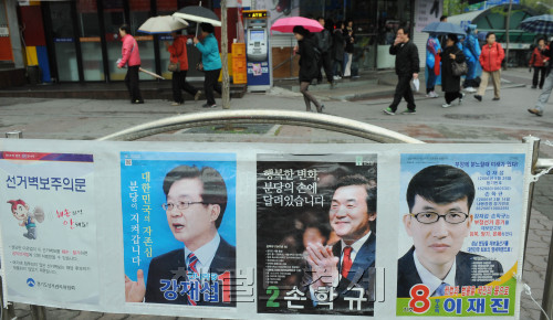 People in the Bundang-B constituency walk past the by-election posters Tuesday, the last day of the electoral campaigns. (Park Hyun-koo/The Korea Herald)