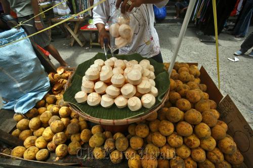 A fruit vendor sells coconuts in Manila. (Bloomberg)