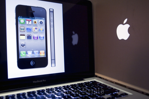 An Apple Inc. iPhone 4 is displayed on a MacBook Pro in Washington, D.C., in the United States. (Bloomberg)