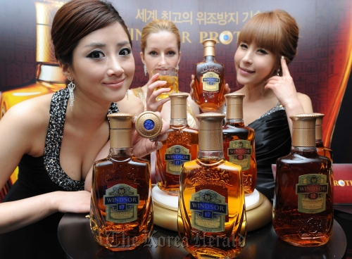 Models pose with Diageo Korea's Windsor whiskies bottled in Windsor Protect bottles in Seoul on Tuesday. (Diageo Korea)
