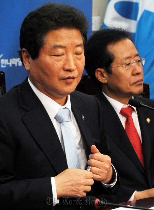 Party leader Ahn Sang-soo (left) and Rep. Hong Joon-pyo of the ruling Grand National Party preside over a supreme council on Thursday following the party's defeat in Wednesday's by-elections. (Yang Dong-chul/The Korea Herald)