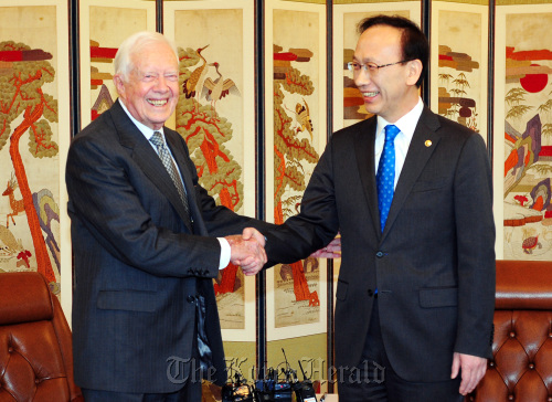 Former U.S. President Jimmy Carter (left) shakes hands with South Korean Unification Minister Hyun In-taek at the headquarters of the inter-Korean talks in central Seoul on Thursday before briefing Hyun on his recent visit to Pyongyang. (Joint Press Corps)