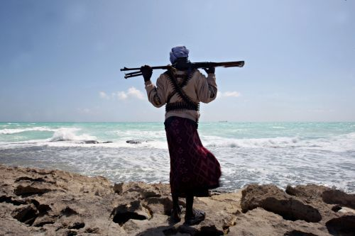In this file photo, an armed Somali pirate along the coastline while the Greek cargo ship, MV Filitsa, is seen anchored just off the shores of Hobyo, northeastern Somalia, where its being held by pirates. (AFP-Yonhap News)