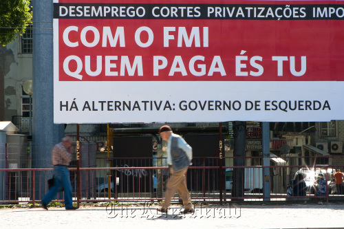 "Pedestrians pass an outdoor advertisement which reads ""With the IMF, it's you who pays,"" in Lisbon. (Bloomberg)"