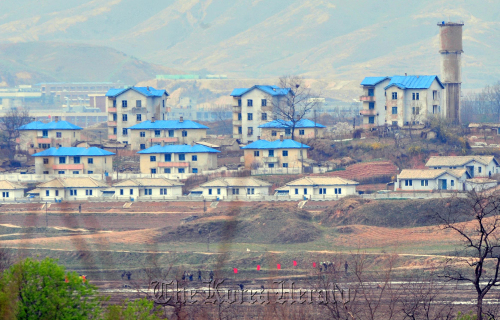 Residents till a field in a North Korean village seen from Panmunjom, Gyeonggi Province. (Yonhap News)