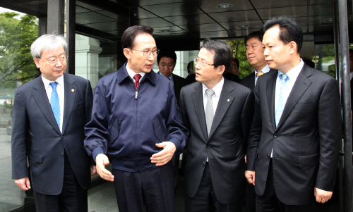 President Lee Myung-bak speaks to Financial Supervisory Service governor Kwon Hyouk-se (right) and Financial Services Commission chairman Kim Seok-dong (left) after rebuking the financial watchdog for complacency during a surprise visit to the FSS on Wednesday in the wake of a financial scandal involving a savings bank in Busan. (Yonhap News)