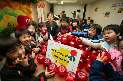 Children at Shinil Kindergarten in Seoul show piggy banks full of cash after raising funds for Community Chest of Korea causes.