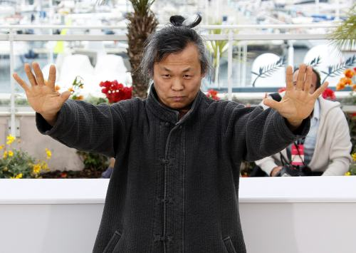 Kim Ki-duk demonstrates martial art-like movements at Cannes Film Festival on Friday. (AFP-Yonhap News)