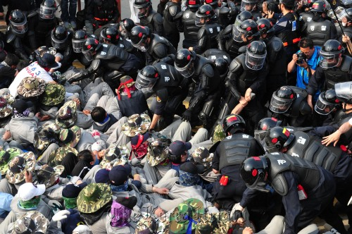 Riot police drag striking workers from Yoosung Enterprise Co. in Asan, South Chungcheong Province, after storming its plant to end union members' illegal strike Tuesday. (Ahn Hoon/The Korea Herald)