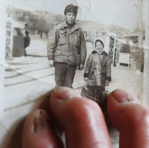 Eum Do-nam, a former South Korean soldier suffering from exposure to a defoliant, touches a photo of him and his daughter at a military base near the Demilitarized Zone in Yeoncheon, Gyeonggi Province. He claims his fingers were deformed by the chemicals. (Yonhap News)