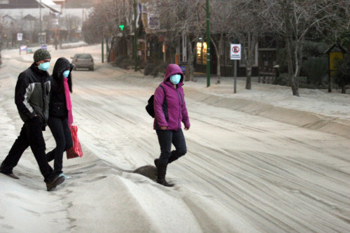 Local residents walk on an ash-covered street in Bariloche, Rio Negro Province, Argentina on Monday. (Xinhua-Yonhap New)