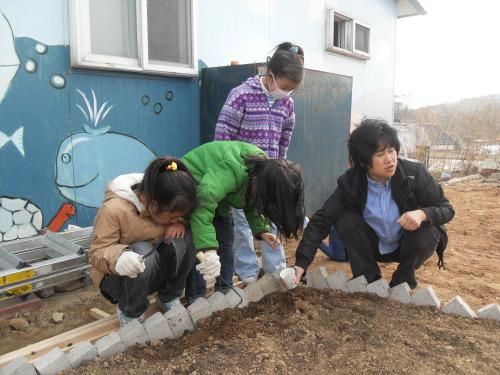 Children and Heemangteo president Jun Jin-kyoung tend the center's garden. (Heemangteo)