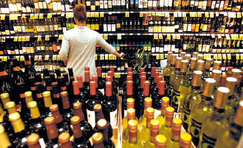 Customer Jennifer Murphy tries to decide on a bottle of wine inside the Ralph's grocery store in downtown Los Angeles, California. (Los Angeles Times/MCT)