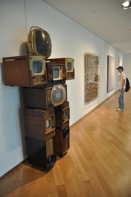 """A visitor looks at artworks at the """"Venice Biennale: the Italian Pavilion in the World"""" exhibition in Seoul. (Yoav Cerralbo/The Korea Herald)"""