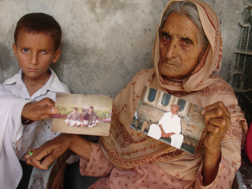 Noor Bibi shows pictures of her husband and son, whom she alleges were picked up by security agencies last week, in Abbottabad, Pakistan on Wednesday. (AP-Yonhap News)