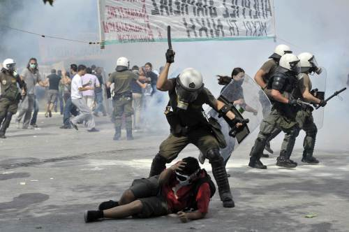 A riot police officer clubs a protester Wednesday during a demonstration near the parliament in the center of Athens. (AFP-Yonhap News)
