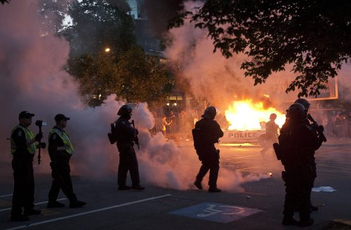 Riot police look on as two police cars burn during a riot in downtown Vancouver, British Columbia Wednesday, June 15, 2011 following the Vancouver Canucks 4-0 loss to the Boston Bruins in game 7 of the Stanley Cup hockey final.(AP-Yonhap News)