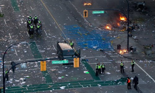 Police officers stand amongst debris after rioters moved through the area following the Vancouver Canucks being defeated by the Boston Bruins in the NHL Stanley Cup Final. (AP-Yonhap News)