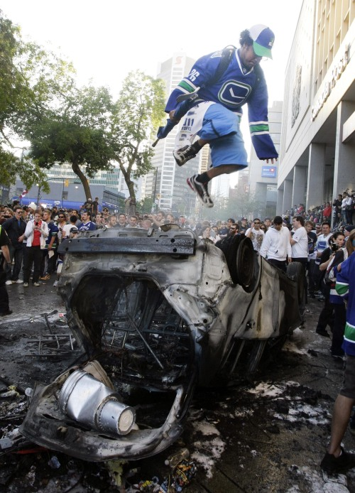 Canucks fans jump onto a destroyed car during a riot in Vancouver, Canada, June 15, 2011. (Xinhua-Yonhap News)