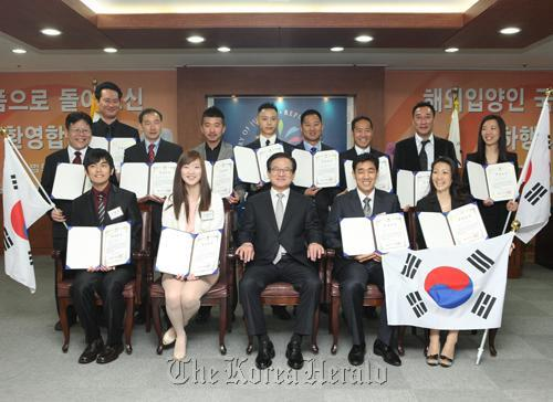 Justice Minister Lee Kwi-nam (front row, center) poses with Korean adoptees who were able to regained Korean citizenship under a new law enacted this year. (Yonhap News)