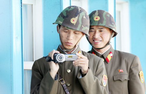 Two North Korean soldiers film with a video camera near the Military Armistice Commission conference room in the Joint Security Area in the truce village of Panmjunjeom on Tuesday as Swedish Defense Minister Sten Tolgfors has an interview with reporters after touring the room. (Yonhap News)