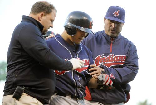Indians right fielder Choo Shin-soo (center) is helped off the field after being hit on the hand by a pitch. (AFP-Yonhap News)