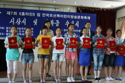 Kang Duk-young (right, second row), CEO of Korea United Pharm, poses with award winners at the Homtamin Cup Korean Chinese Children's Broadcasting Culture Festival in Harbin, Heilungjiang Province on Sunday.