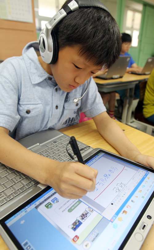 A student writes a note on a tablet computer during a class at a Seoul elementary school designated as a pilot school using digital textbooks. (Yonhap News)