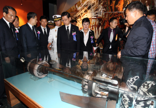 Prime Minister Kim Hwang-sik (third from right) and other participants in a ceremony to mark the anniversary of a 2002 naval skirmish look at a North Korean torpedo part ― used to attack the warship Cheonan last year ― on display in Pyeongtaek, Gyeonggi Province, Wednesday. (Yonhap News)