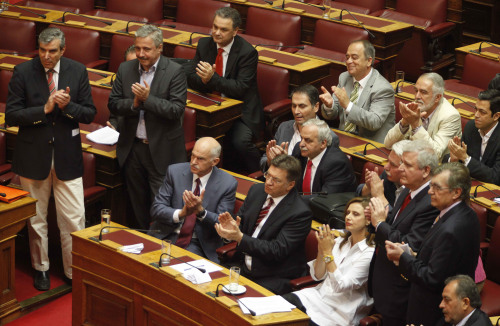 Greek Prime Minister George Papandreou (first left seated), applauds with his party parliament members, after they vote the new austerity measures in the Greek Parliament in Athens on Wednesday. (AP-Yonhap News)