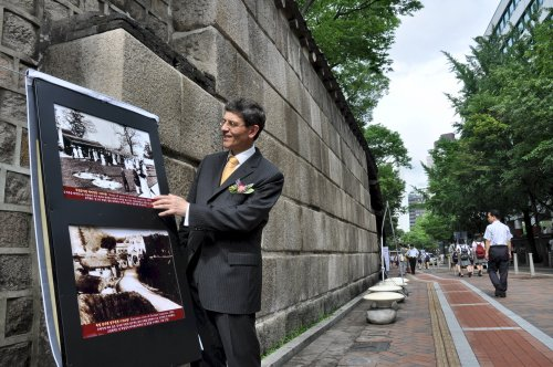 German Ambassador Hans-Ulrich Seidt stands in front of the remnants of a bridge, which connected the former German Legation with Deoksu Palace, while discussing a picture taken in what could have been the last German diplomatic garden party before the annexation of Korea. (Yoav Cerralbo/The Korea Herald)